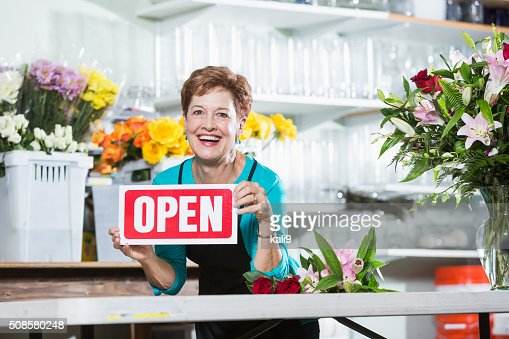 Mature woman in flower shop holding OPEN sign : Stock Photo