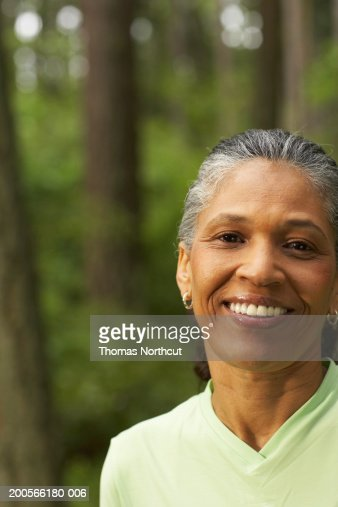 Mature woman in forest, smiling, portrait, close-up : Stock Photo