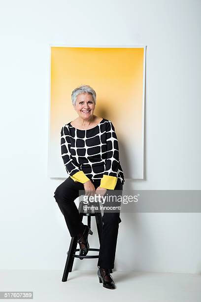 Mature woman in funky dress and yellow background
