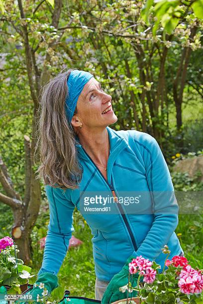 Mature woman in garden looking up