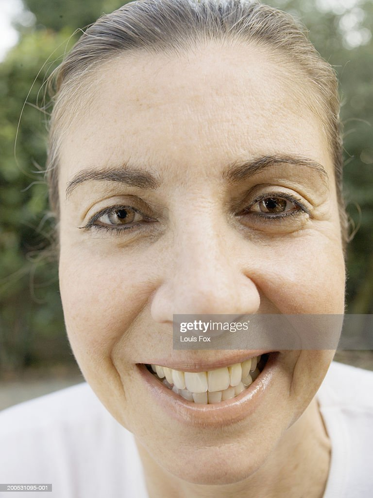 Mature woman in garden, smiling, portrait, close-up : Stock Photo