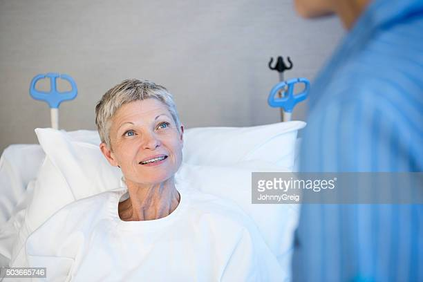 Mature woman in hospital bed smiling, portrait