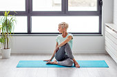 Mature woman in joga pose exercise in appartment at rug with window on background
