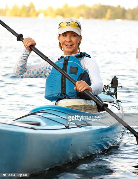 Mature woman in kayak wearing life jacket, smiling, portrait