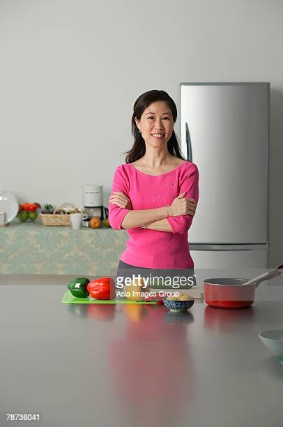 Mature woman in kitchen, arms crossed, looking at camera
