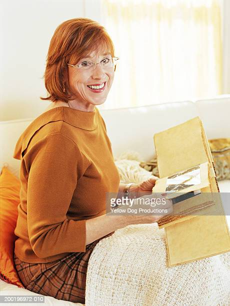 Mature woman in living room holding photo album, smiling