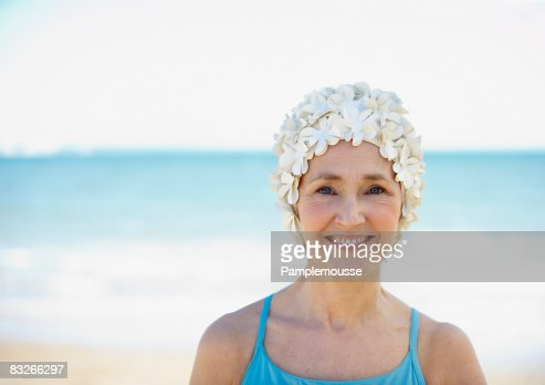 Mature woman in old-fashioned swim cap on beach