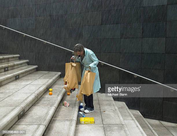 Mature woman in rain holding split bags, groceries spilling over steps