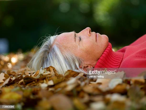 Mature woman in red pullover lying on autumn leaves, close-up