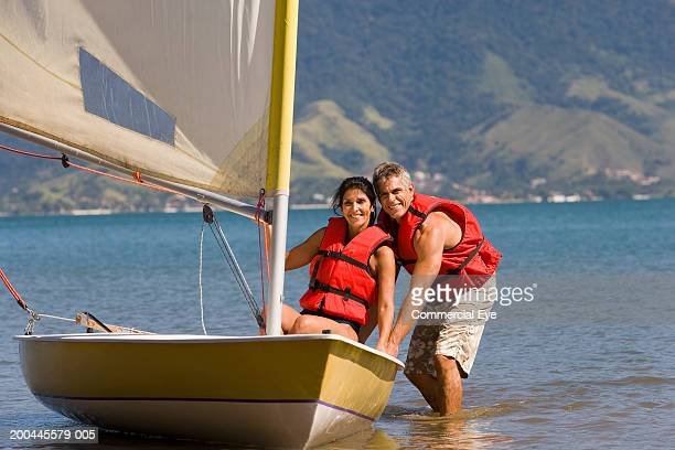 Mature woman in sailboat, man in water guiding sailboat