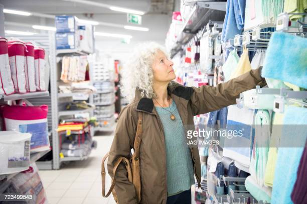 Mature woman in supermarket, looking at homeware section