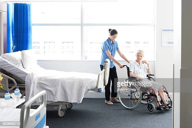 Mature woman in wheelchair with nurse in hospital room