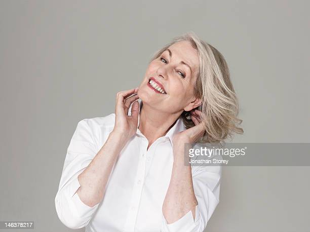 Mature woman in white shirt flicking her gray hair