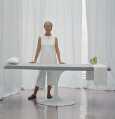 Mature woman in white standing next to massage table