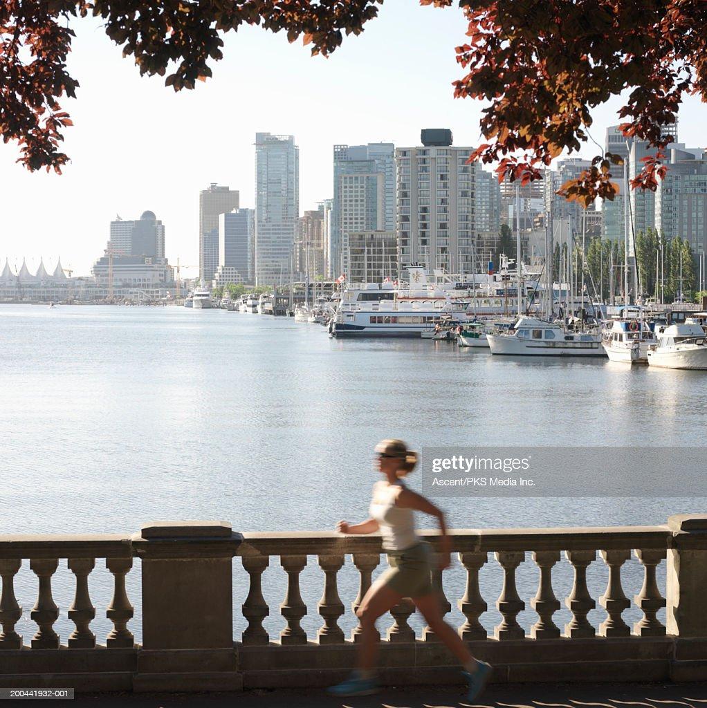 Mature woman jogging along waterfront, sunrise (blurred motion) : Stock Photo