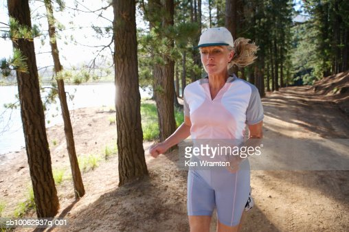 Mature woman jogging in forest : Stock Photo