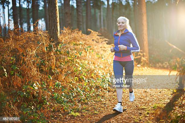 Mature woman jogging on forest path