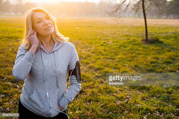 Mature woman jogging with Music as motivation for runnng