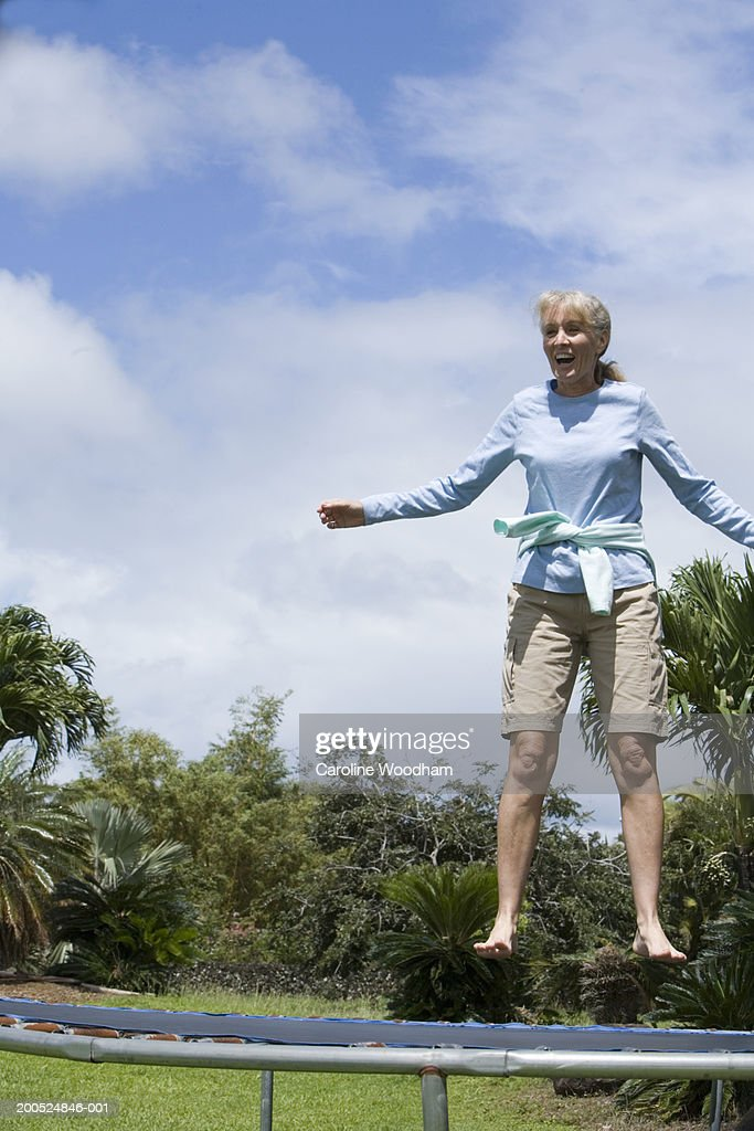 Mature woman jumping on trampoline, low angle view : Stockfoto