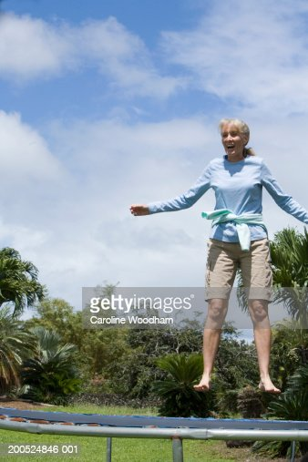 Mature woman jumping on trampoline, low angle view : Bildbanksbilder