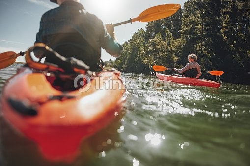Mature woman kayaking in lake on a sunny day : Stock Photo