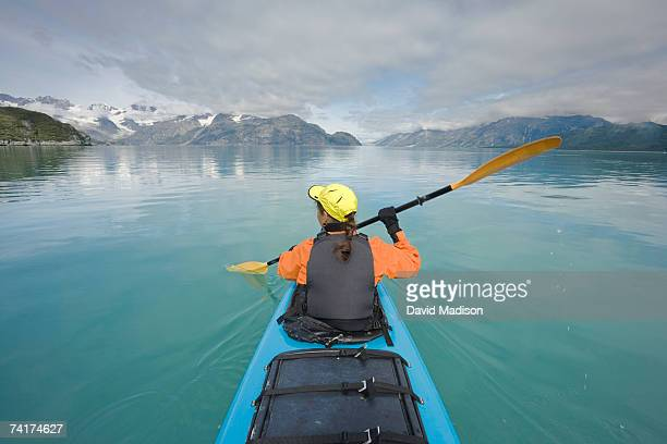 'Mature woman kayaking, rear view'