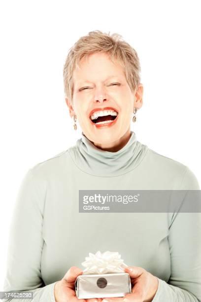 Mujer madura Riendo y sosteniendo un regalo.