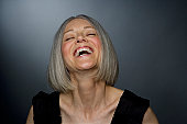 Mature woman laughing, eyes closed, close-up