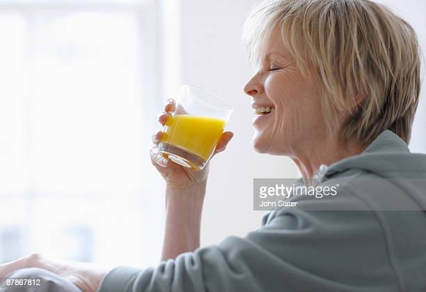 mature woman laughing holding glass of juice