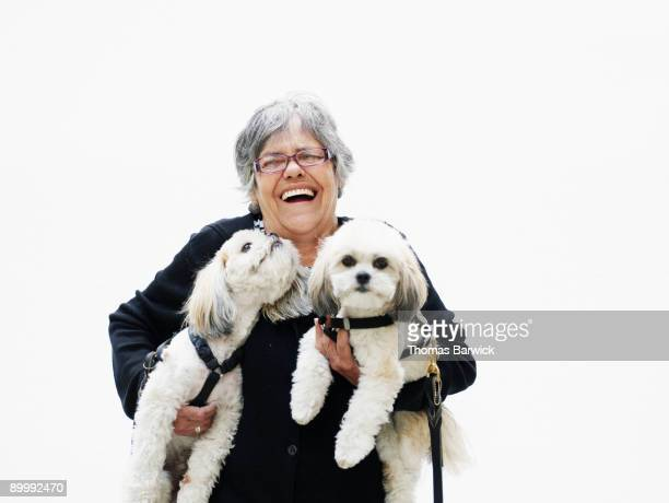 Mature woman laughing holding two dogs