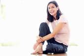 Full length of cheerful mature woman sitting on floor - copyspace