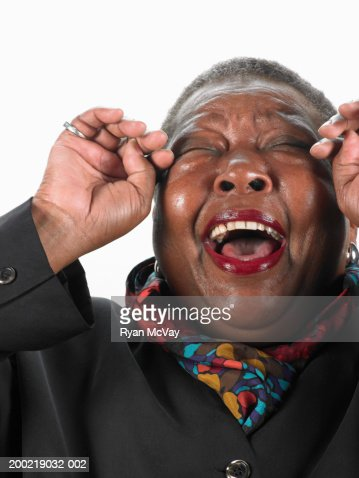 Mature woman laughing, wiping tears from eyes