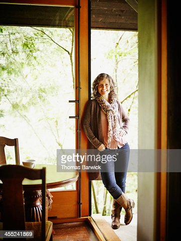 Mature woman leaning against doorway of cabin