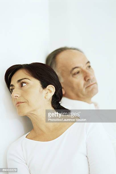 Mature woman leaning against husband, both looking away