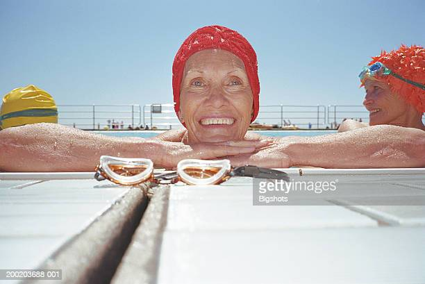 Mature woman leaning against side of swimming pool, smiling, portrait