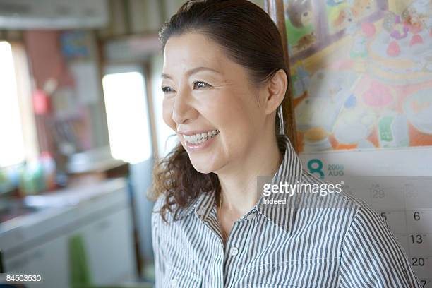 Mature woman leaning by wall, smiling, portrait