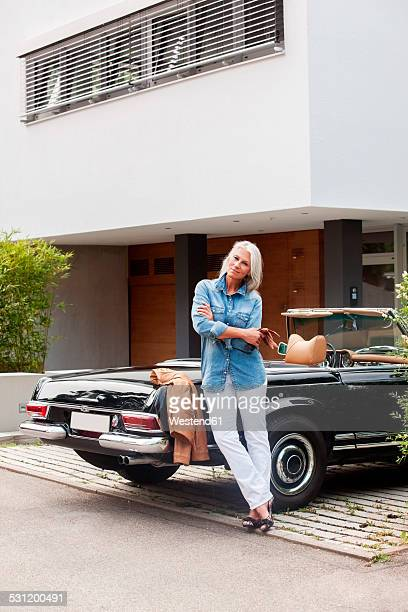 Mature woman leaning on convertible car in front of her one-family house