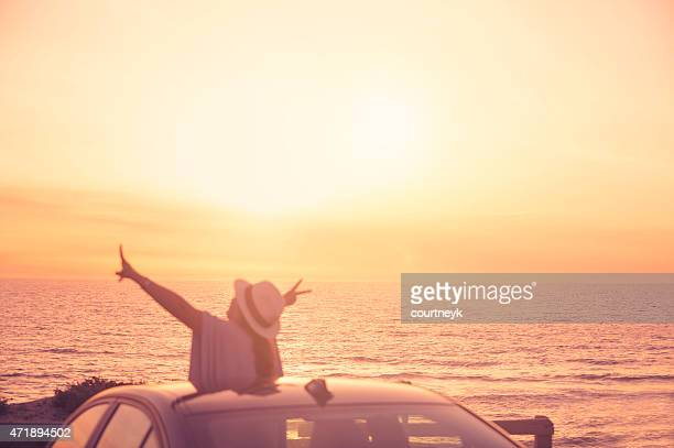 Mature woman leaning out of sunroof at sunset.