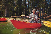 Portrait of mature woman learning to row in kayak with help from a man. Man pushing the kayak from behind while woman paddling in the lake.