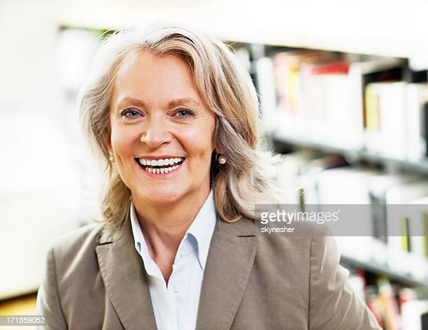 Mature woman librarian looking at camera.