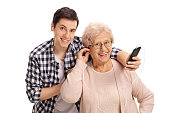Mature woman listening to music on a phone with her grandson isolated on white background