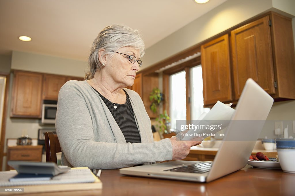 Mature Woman Looking at Household Bills : Stock Photo