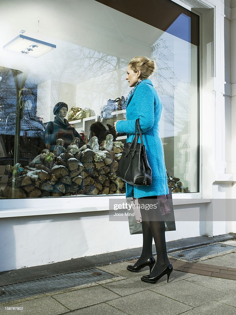 mature woman looking into clothing shop window : Stock Photo