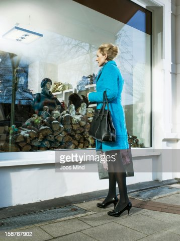 mature woman looking into clothing shop window : Foto de stock
