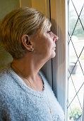 Close up vertical image of a mature woman looking out of a window