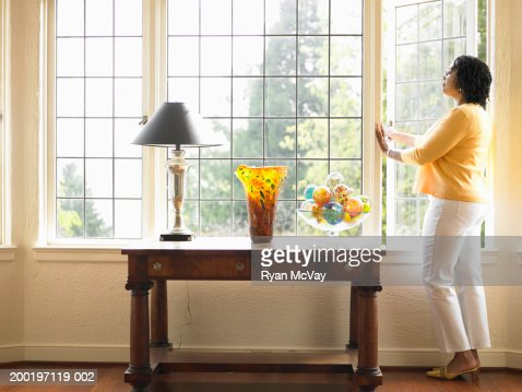 Mature woman looking out open window in living room, side view : Stock Photo