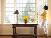 Ältere Frau und schaut nach draussen offenen Fenster im Wohnzimmer