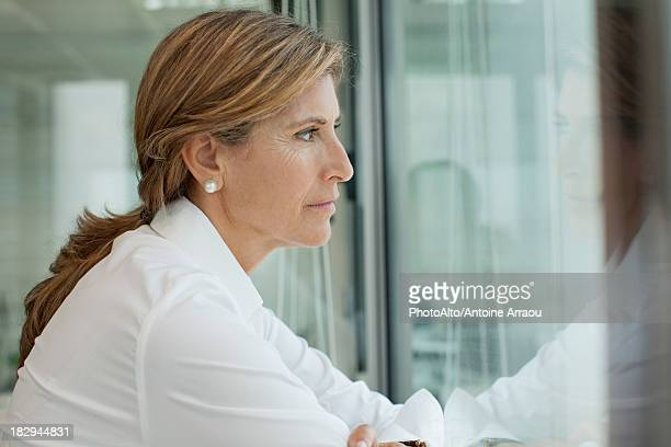 Mature woman looking out window, portrait