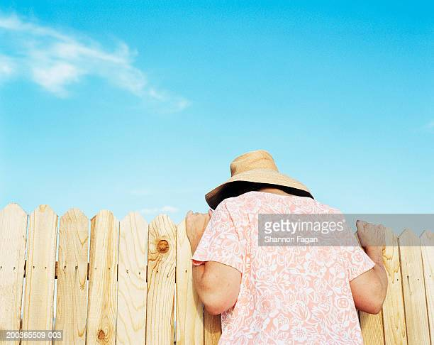 Mature woman looking over fence, rear view