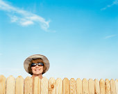 Mature woman looking over fence, smiling